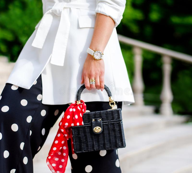 Fashionable bag close-up in female hands.Girl walks in the city outdoors. Stylish modern and feminine image, style. stock images