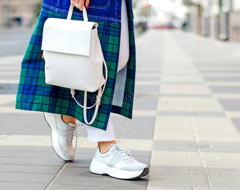 Fashionable bag close-up in female hands.Girl walks in the city outdoors. Stylish modern and feminine image, style. stock photo