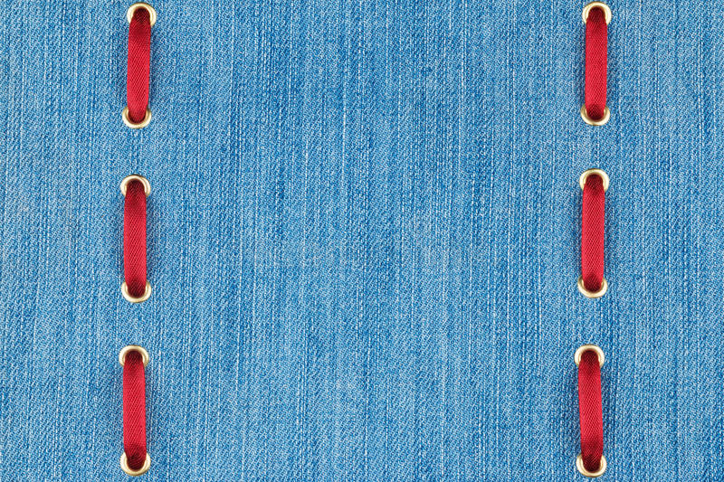 Fashionable beautiful background, red satin ribbon inserted in denim, with space for your creativity. royalty free stock photography