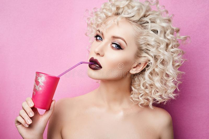 Fashionable and beautiful blonde model girl with blue eyes and with professional bright makeup, drinks by a straw from a pink glas stock images