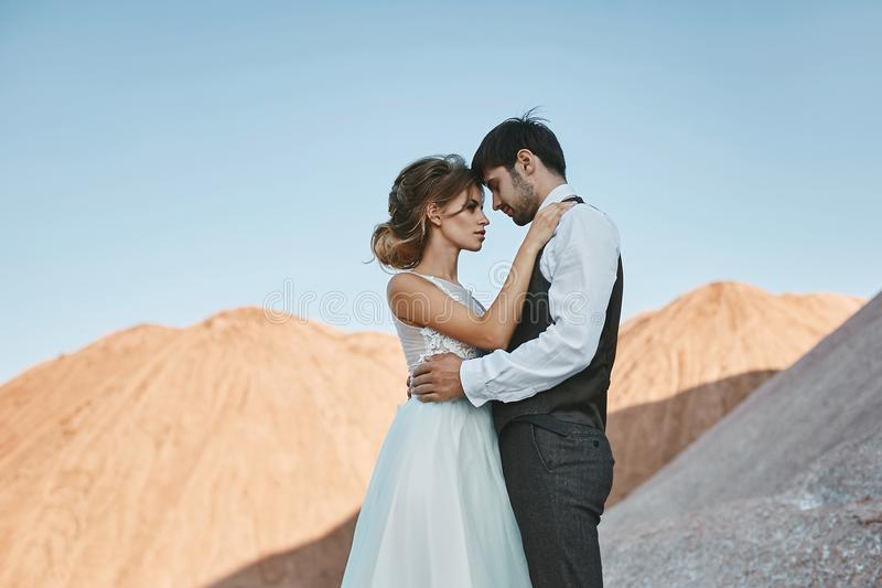 Fashionable and beautiful couple, and elegant blonde model girl with stylish hairstyle, in white lace dress and stock photography