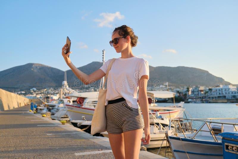 Fashionable beautiful girl teenager walking on pier, sunset on sea stock photo