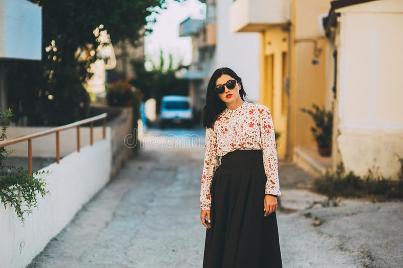 The fashionable beautiful girl walks around the city. In a summer dress royalty free stock photography