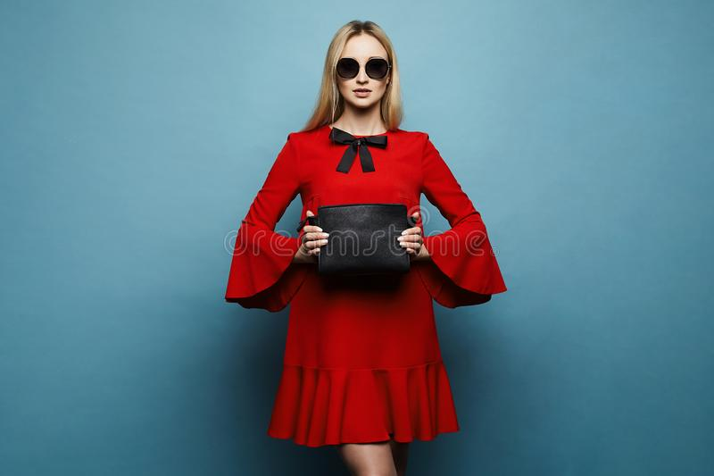Fashionable and beautiful model blonde girl with professional makeup, in stylish sunglasses and in glamorous red dress stock photography