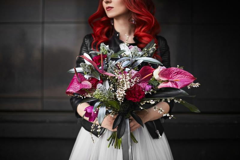Fashionable and beautiful model girl with red hair and bright makeup, in a white wedding dress and in a leather jacket royalty free stock image