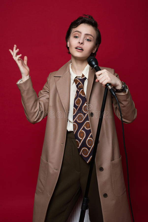 Fashionable beautiful singer girl in retro coat, tie and pants with microphone in hands posing on red background. royalty free stock photos