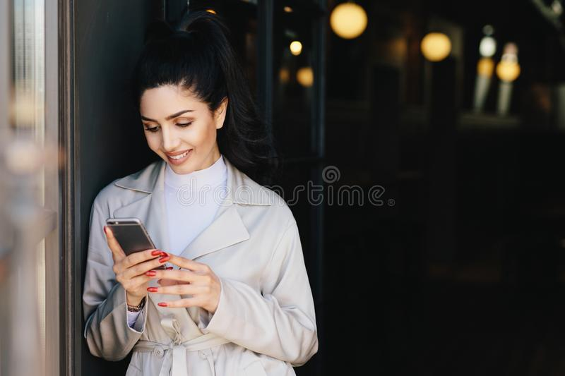 Fashionable beautiful woman with dark hair tied in pony tail dressed in white elegant coat holding cell phone looking into screen royalty free stock image