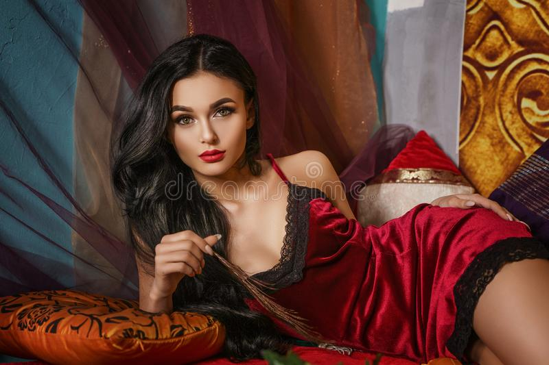 Fashionable beautiful woman lies in a red negligee royalty free stock photo