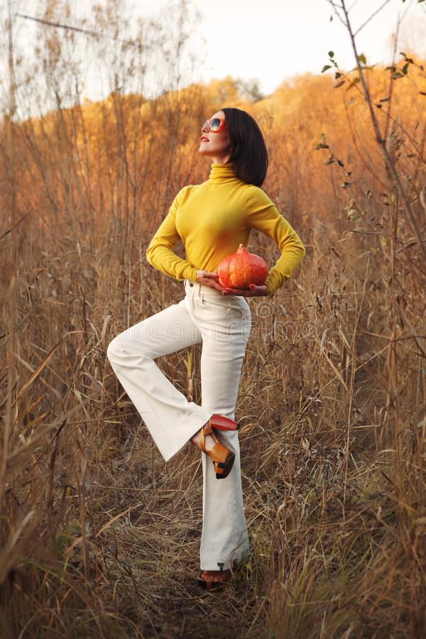 Fashionable beautiful woman in sunglasses standing in the field and holding a pumpkin for Halloween. She`s wearing white bell bottom pants and yellow jacket stock photos