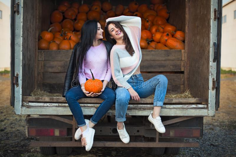 Fashionable beautiful young girlfriends together at the autumn pumpkin patch background. Having fun and posing royalty free stock photo