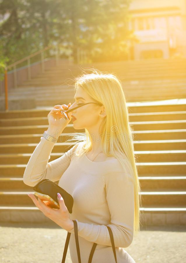 Fashionable blond girl. In beige dress tries on glasses royalty free stock photography