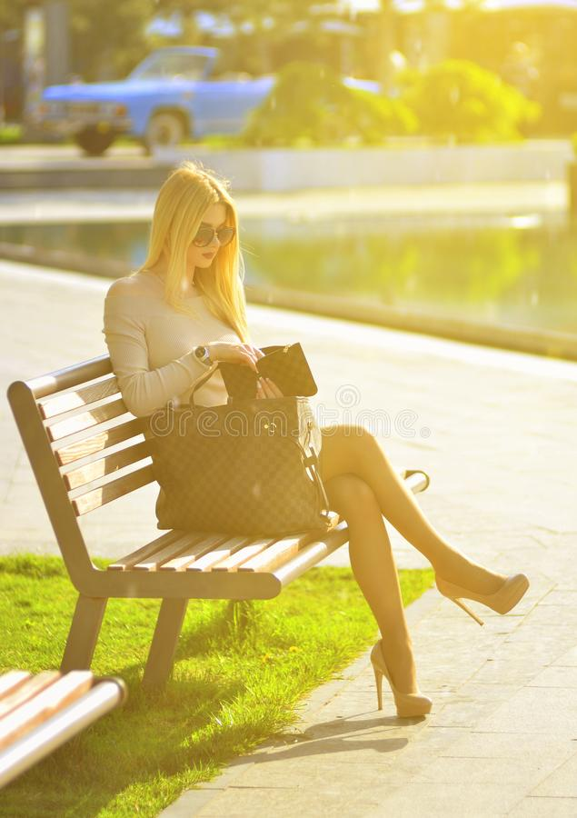 Fashionable blond girl in a dress and sunglasses is sitting on a bench and crouching in a cosmetic bag. The concept of a luxurious life. Street fashion royalty free stock image