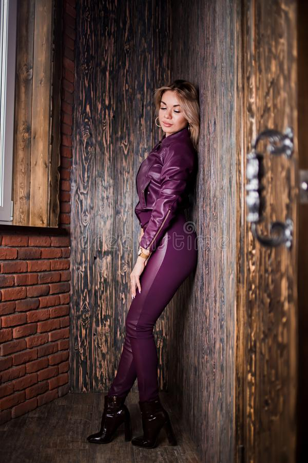 Fashionable blond woman in sunglasses, trendy clothes, high heel boots with sexy figure posing near open door of cafe bar. Lifestyle, spring, fashion portrait royalty free stock photography