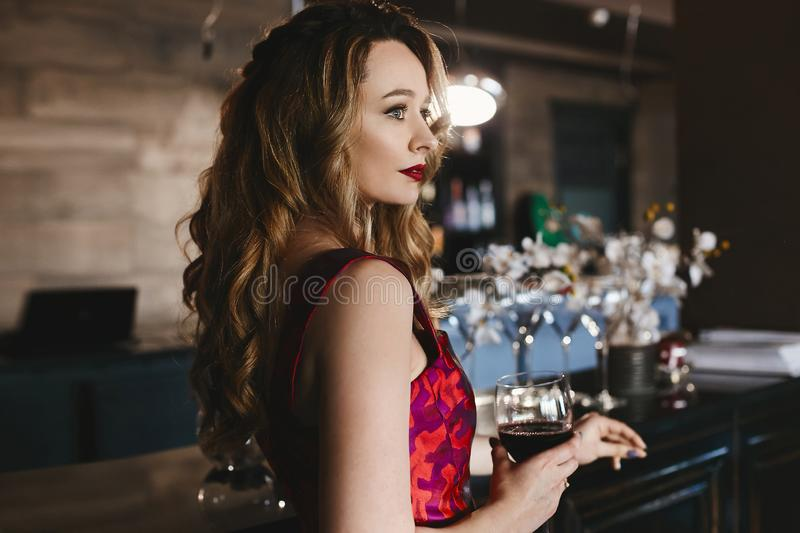 Fashionable blonde model girl with red lips and with curly hairstyle, in the red-pink dress stands at the bar with. Glass of a red wine in her hand and posing royalty free stock photo