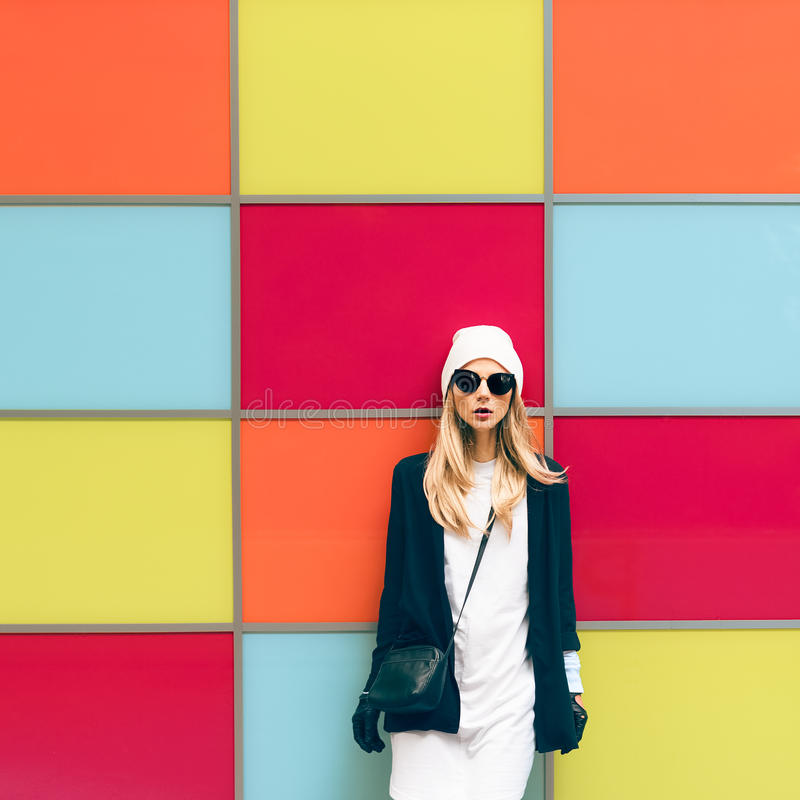 Fashionable blonde standing against a bright wall royalty free stock images