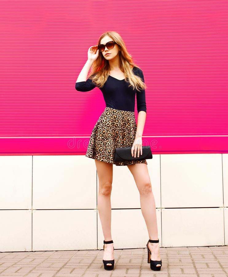Fashionable blonde woman model posing in leopard skirt, sunglasses with handbag clutch on city street royalty free stock images