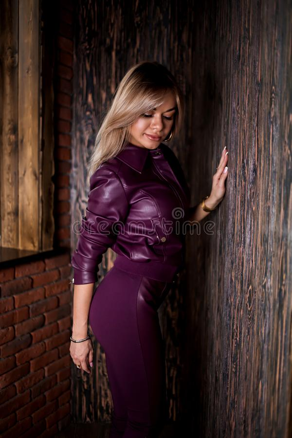 Fashionable blond woman in sunglasses, trendy clothes, high heel boots with sexy figure posing near open door of cafe bar. Fashionable blonde woman trendy royalty free stock photo