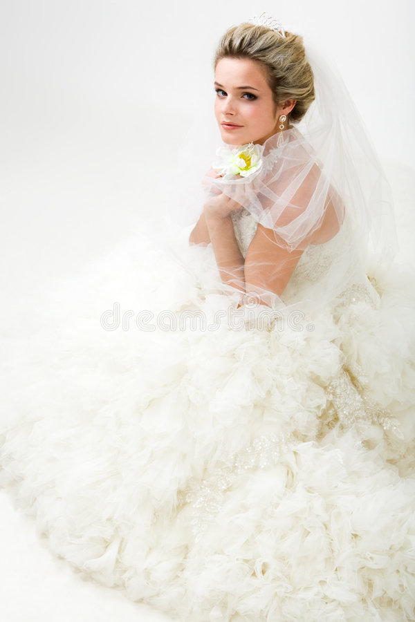 Fashionable bride. Photo of elegant bride in fashionable wedlock with flower in hand sitting and looking at camera royalty free stock photos
