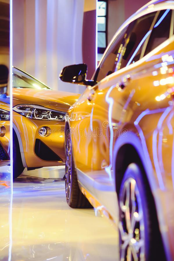 Fashionable bright auto show A number of new cars parked in the car dealers` warehouse, modern design of the room with mirrors royalty free stock image