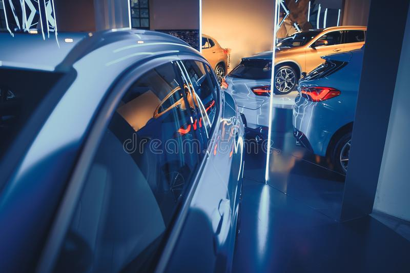 Fashionable bright auto show A number of new cars parked in the car dealers` warehouse, modern design of the room with mirrors stock photography