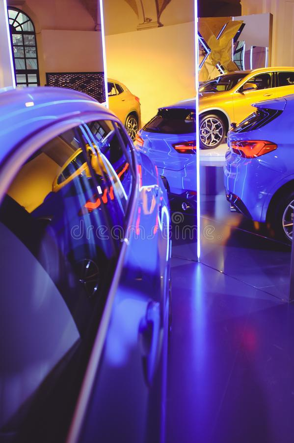 Fashionable bright auto show A number of new cars parked in the car dealers` warehouse, modern design of the room with mirrors royalty free stock photo