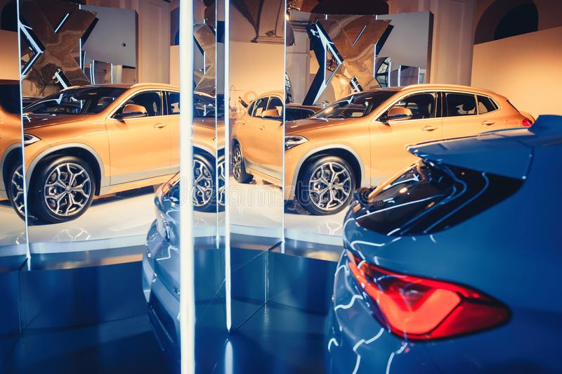 Fashionable bright auto show A number of new cars parked in the car dealers` warehouse, modern design of the room with mirrors royalty free stock photos