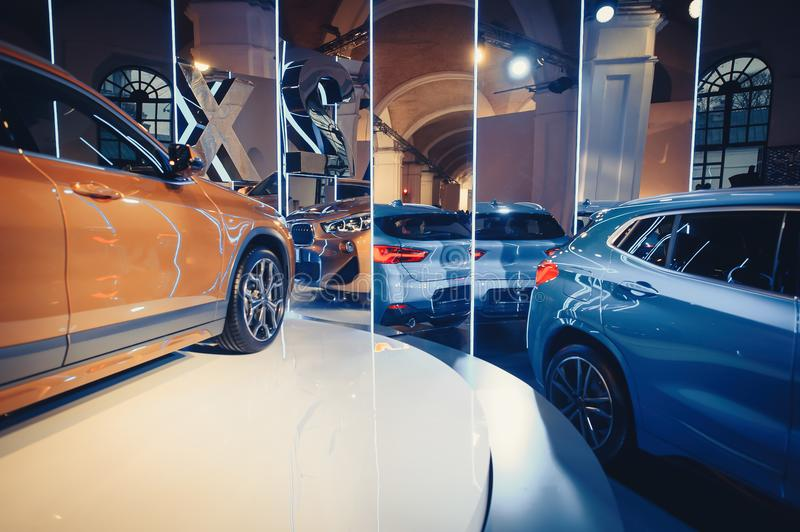 Fashionable bright auto show A number of new cars parked in the car dealers` warehouse, modern design of the room with mirrors stock photos