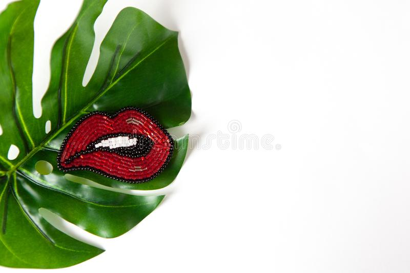 Fashionable brooch in the shape of lips from Japanese beads on green leaf of Monstera on white background. Close-up, flat lay royalty free stock images