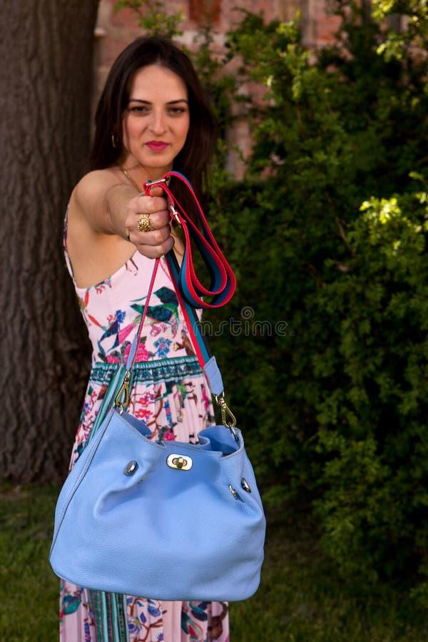 Brunette woman blue hand bag tree brick wall, Groot Begijnhof, Leuven, Belgium stock images