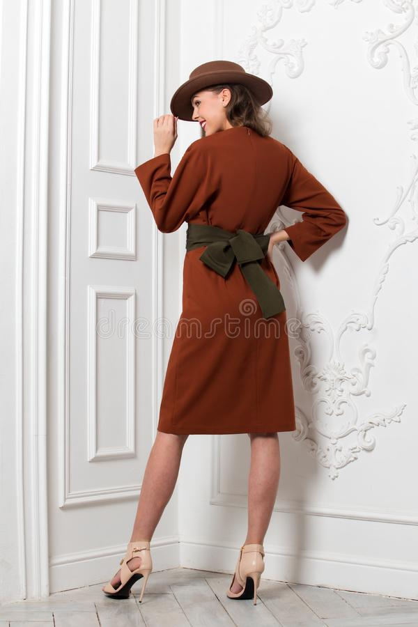 Fashionable charming girl dressed in brown dress with a wide belt and a brown hat poses against a white wall in the room royalty free stock images