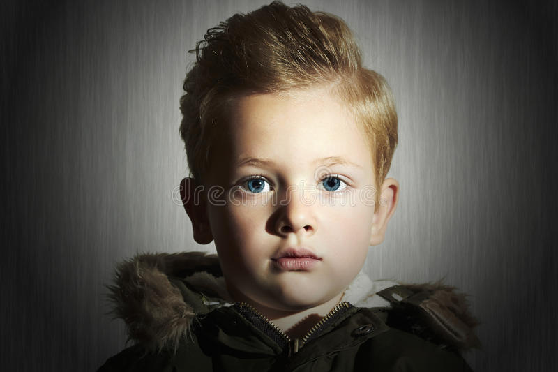 Fashionable child in winter coat. fashion kid.children.khaki parka.little boy hairstyle. Lose-up portrait of Fashionable child in winter coat. fashion kid stock images