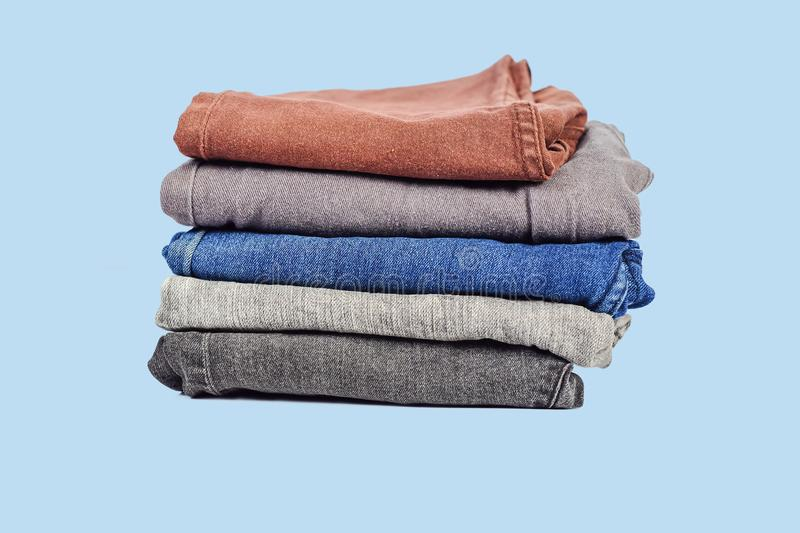 Fashionable clothes, pile of jeans. On background royalty free stock images