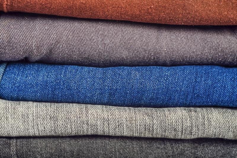 Fashionable clothes, pile of jeans. On background royalty free stock image