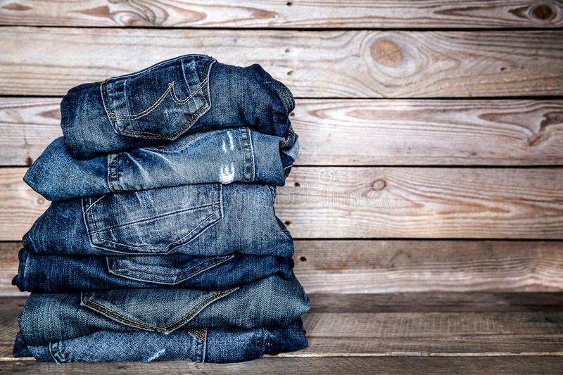 Fashionable clothes. pile of jeans on a wooden background royalty free stock photo