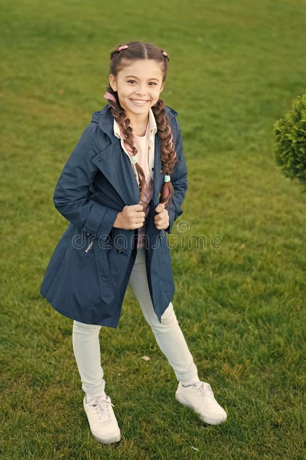 Fashionable coat. Girl cute face braided hair posing coat in spring park. Clothing for spring walks. Little fashion. Model. Clothes and accessory. Kid wear royalty free stock photos