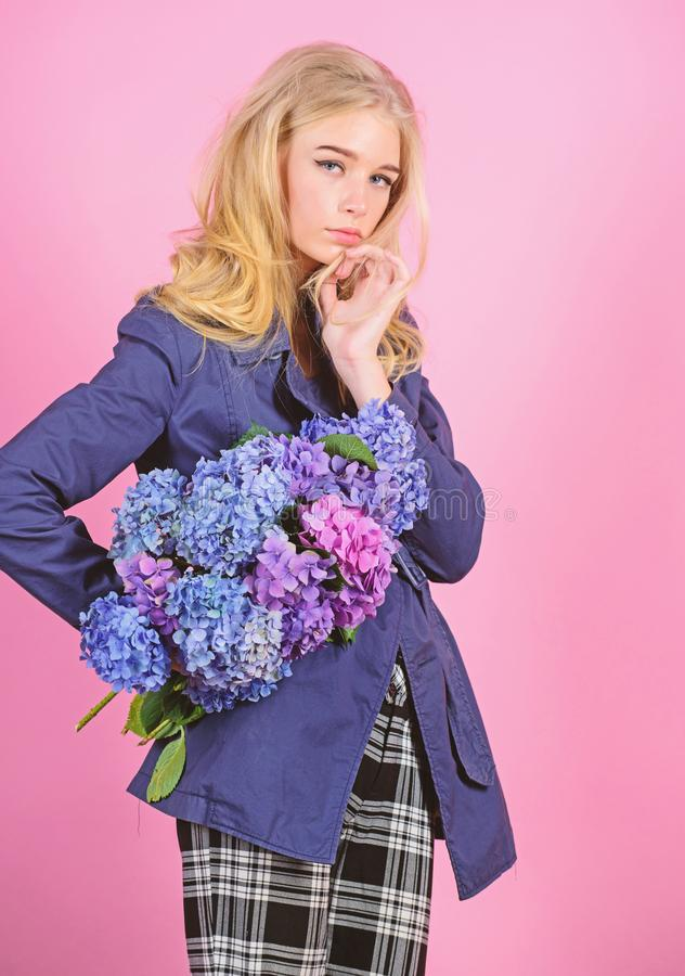 Fashionable coat. Must have concept. Clothes and accessory. Woman blonde hair posing coat with flowers bouquet. Girl. Fashion model wear coat for spring and stock images