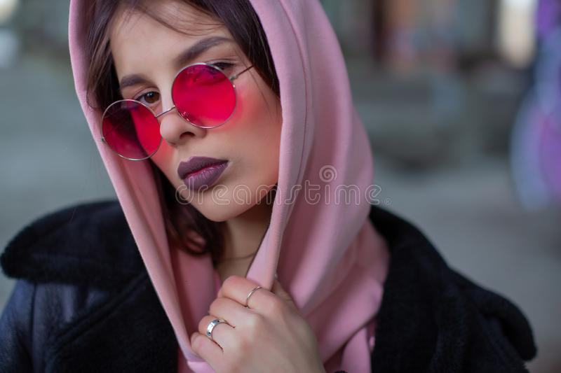 Cool girl in a powdery hoodie and red glasses royalty free stock image