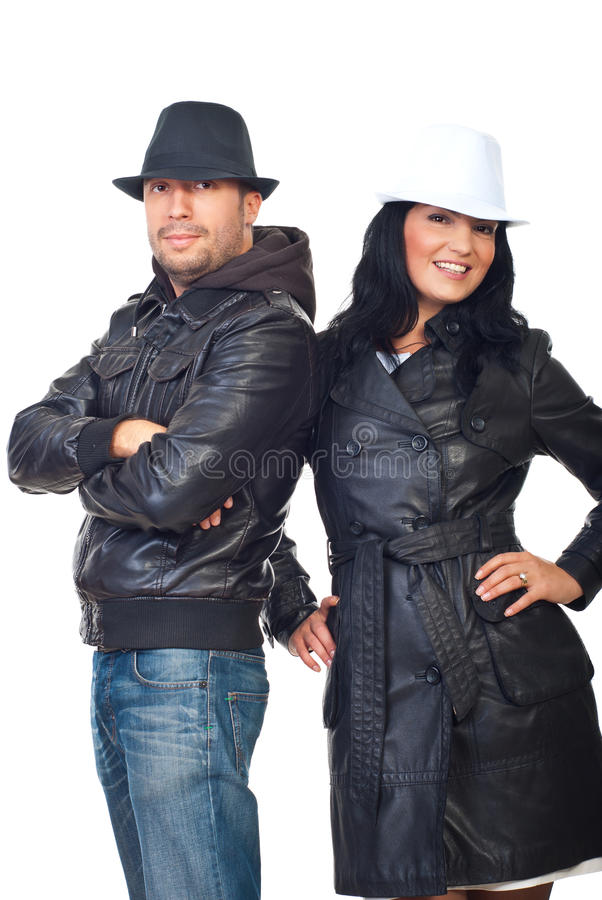 Fashionable couple in leather coats and hats royalty free stock photography