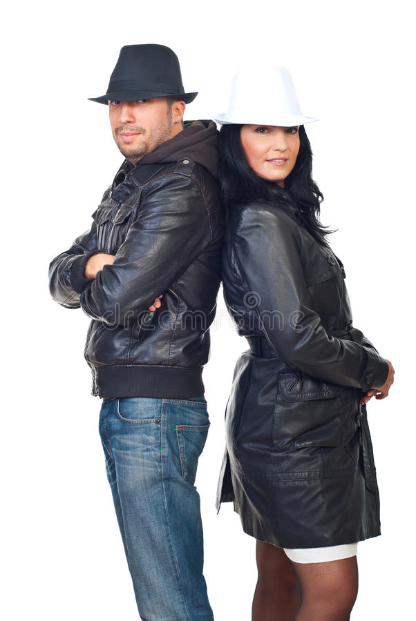 Fashionable couple in leather jackets and hats stock photos