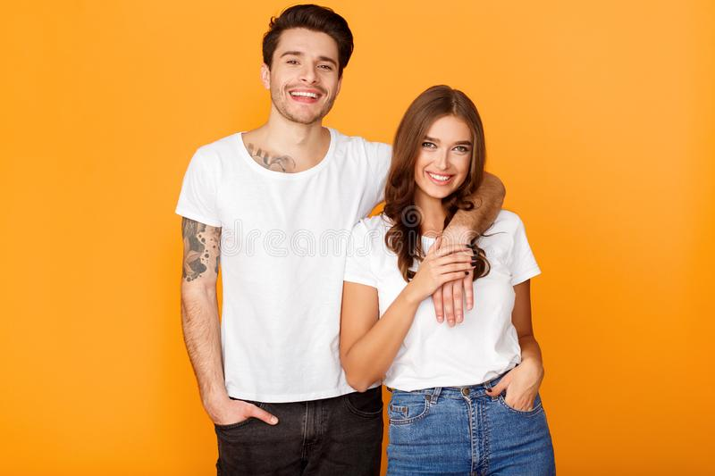 Fashionable couple posing over yellow studio background stock photography
