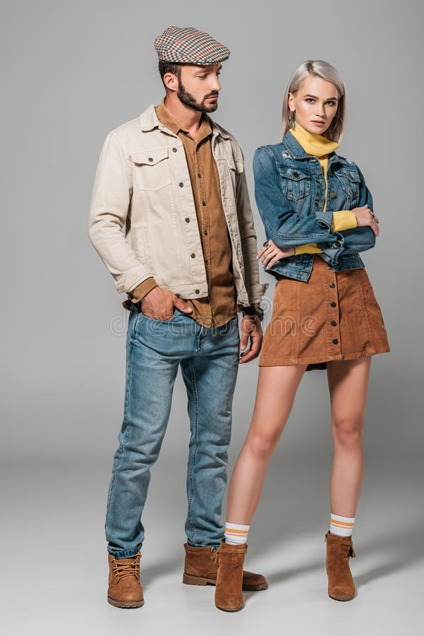 Fashionable couple posing in street style autumn outfit. On grey stock image