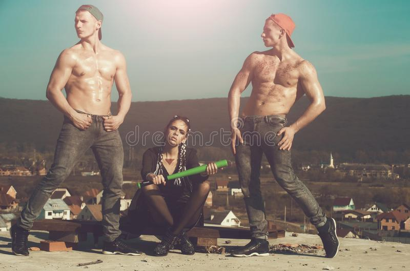 Fashionable criminal woman and muscular men with baseball bat royalty free stock photos