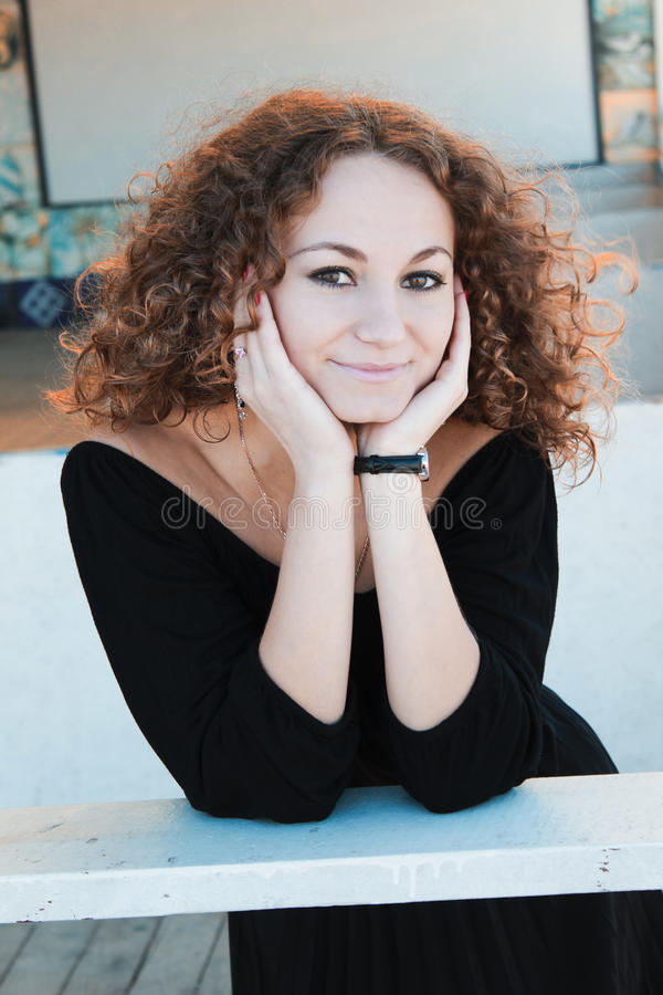 Fashionable curly brunette model posing. Fashionable beautiful curly brunette model in pink dress posing stock photos