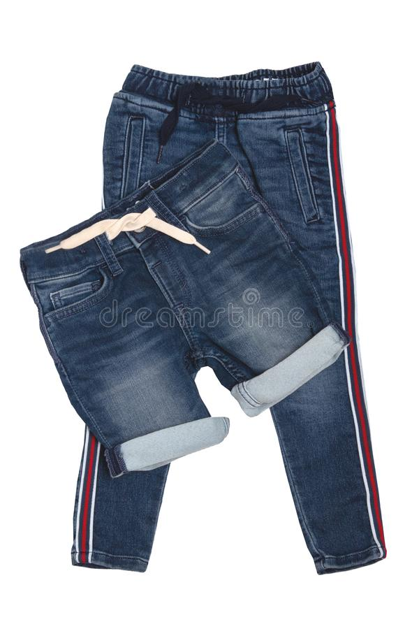 Fashionable denim clothes. Trendy stretch blue jeans trousers and a stylish short jeans pants with white ribbon isolated on a. White background. Fashionable stock photo