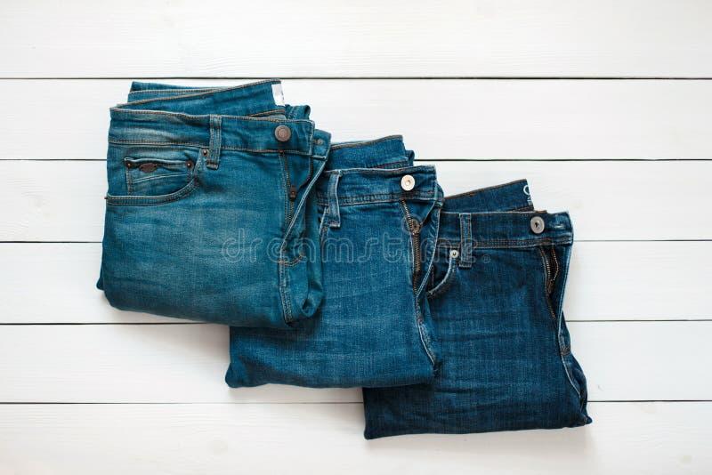 Fashion denim pants lie on a wooden white table. Fashionable different colors denim trousers lie on a wooden white table stock photo