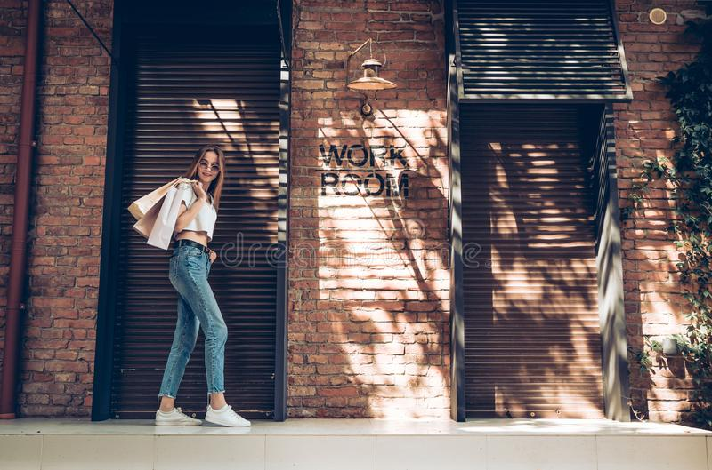Fashionable dressed young woman with shopping bags posing near brown metal shutters background stock image