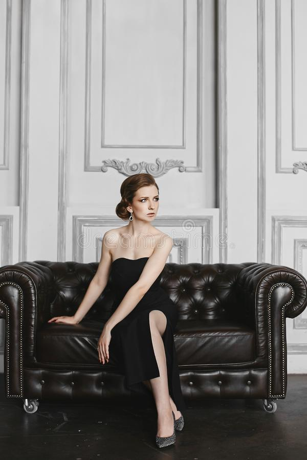 Fashionable and elegant brunette model girl with gentle make-up an big earrings, in long black dress, sits on the vintage sofa and stock photos