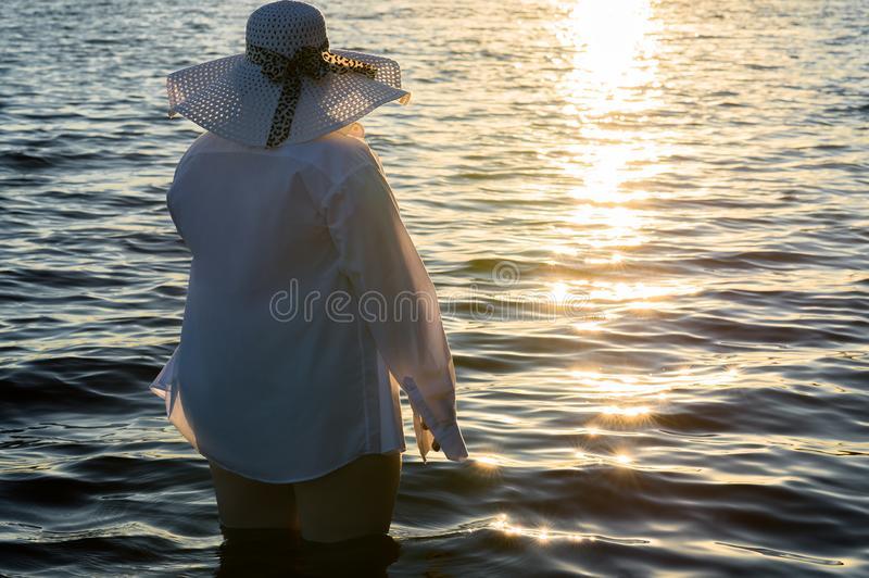 Fashionable fat woman standing in water on sunset. Fashionable adult fat woman standing in water on sunset outdoors royalty free stock image