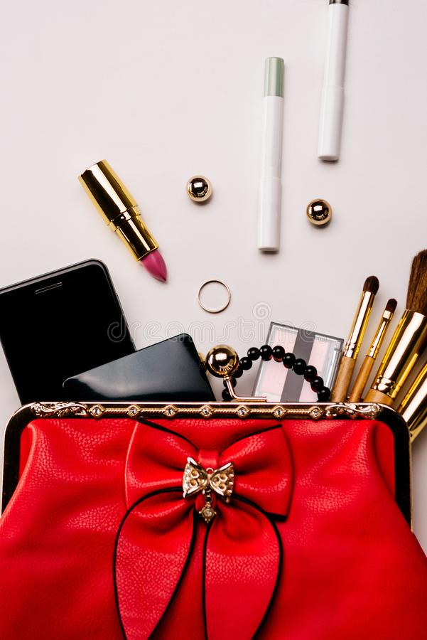 Fashionable female accessories brushes smartphone lipstick eyeshadow and red bag stock photography