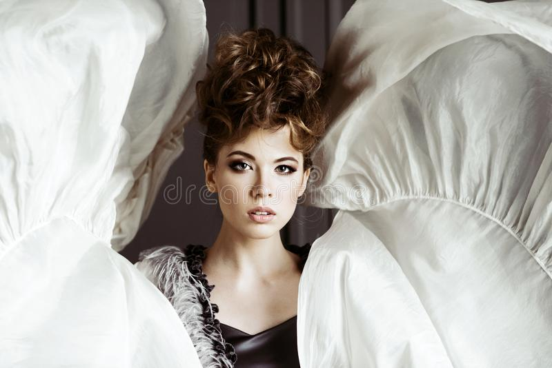 Fashionable female portrait of cute lady in dress indoors. Close up beautiful model girl in elegant pose. Closeup beauty blonde woman with hairstyle and makeup royalty free stock photography